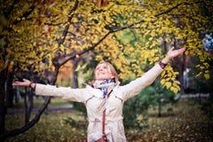 Höstkvinnan som är lycklig i nedgång, parkerar att se runt om att ha gyckel som ler i härlig färgrik skoglövverk Royaltyfri Bild