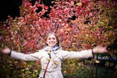Höstkvinnan som är lycklig i nedgång, parkerar att se runt om att ha gyckel som ler i härlig färgrik skoglövverk Royaltyfria Bilder
