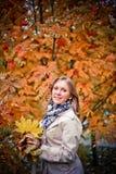 Höstkvinnan som är lycklig i nedgång, parkerar att se runt om att ha gyckel som ler i härlig färgrik skoglövverk Arkivbilder