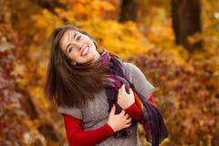 Höstkvinnastående som utomhus ler på parkera Royaltyfri Bild