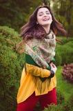 Höstkvinnastående som utomhus ler på parkera Arkivfoto
