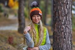 Höstlandskap, en flicka i hatt, med långt anseende för blont hår med henne tillbaka, på kusten av en sjö Arkivbilder