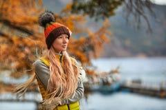 Höstlandskap, en flicka i hatt, med långt anseende för blont hår med henne tillbaka, på kusten av en sjö Arkivbild