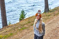 Höstlandskap, en flicka i hatt, med långt anseende för blont hår med henne tillbaka, på kusten av en sjö Arkivfoton