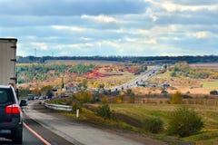 Höstlandskap med biltrafik vid huvudvägvägen som är utgående till horisonten Arkivbilder