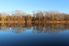 Höstlandskap med reflexion av träd i floden arkivbilder