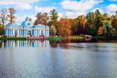 Höstlandskap med sikt över en trädgårds- ` för paviljong`-grotta och puckelryggbron i Catherine Park, Pushkin, helgon Royaltyfria Foton