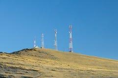 Höstlandskap med torn för en telekommunikation överst av en kulle som täckas med torrt gult gräs fotografering för bildbyråer