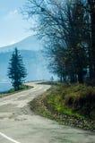 Höstlandskap, vägen som leder in i bergen, blå moun Arkivfoton