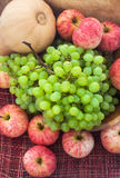 Höstliga mogna frukter och veg - grön druva, röda äpplen och pumpk Royaltyfri Bild