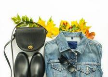 Höstmode, kvinnahöstdräkt på vit bakgrund Blått grov bomullstvillomslag, retro solglasögon, svart crossbody påse, svart regnbu royaltyfria foton