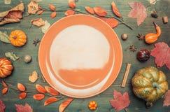 Höstsammansättning, gulingsidor, små pumpor fodrade runt om den bruna plattan, utrymme för den lekmanna- textlägenheten royaltyfria bilder