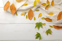 Höstsammansättning med gulingsidor och en varm halsduk Höst Time På en vit trätabell bästa sikt med utrymme för inskrift arkivfoton