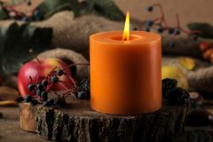 Höstsammansättning med stearinljus och höstfrukter och bär och kastanjer på en trätabell royaltyfri foto