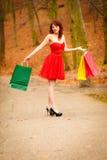 Höstshopparekvinnan med försäljning hänger löst utomhus- parkerar in Arkivfoto
