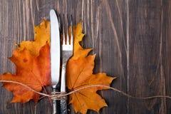 Höstsidor, kniv och gaffel arkivbild