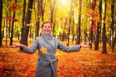 Höstsidor som faller på lycklig ung kvinna i färgglade Forest Park höstlig mood fall arkivbilder