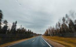 Höstskogväg på snabbt drev Sikt från vindrutan med droppar Arkivfoto