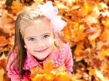 Höststående av den förtjusande lilla flickan med lönnlöv Arkivfoto