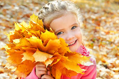 Höststående av den gulliga le lilla flickan med lönnlöv Royaltyfri Foto