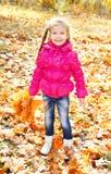 Höststående av den gulliga le lilla flickan med lönnlöv Royaltyfri Bild