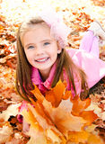 Höststående av den gulliga le lilla flickan med lönnlöv Royaltyfria Bilder