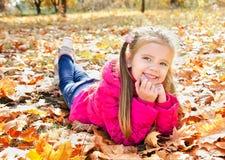 Höststående av den gulliga lilla flickan som ligger i lönnlöv Arkivfoto