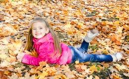 Höststående av den gulliga lilla flickan som ligger i lönnlöv Fotografering för Bildbyråer