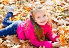 Höststående av den gulliga lilla flickan som ligger i lönnlöv Royaltyfri Bild