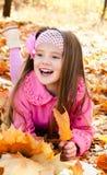 Höststående av den lyckliga lilla flickan med lönnlöv Royaltyfri Foto