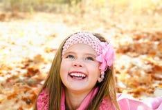 Höststående av den lyckliga lilla flickan med lönnlöv Royaltyfri Fotografi