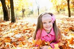 Höststående av den lyckliga lilla flickan med lönnlöv Arkivbild