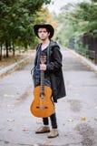 Höststående av den unga grabben med gitarren arkivfoto