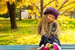 Höststående av det härliga barnet Lycklig liten flicka med sidor i parkera i nedgång arkivbilder