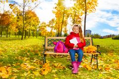 Höststående av lilla flickan på bänken Arkivfoto