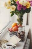 Höststilleben, muttrar, citrusfrukter och bok Arkivfoto