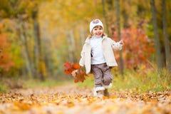 Hösttid, behandla som ett barn lyckliga små, flickan promenerar banan med en bukett av höstsidor Arkivfoto