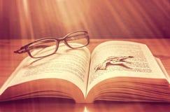 Hösttjänstledigheter på den öppnade boken med exponeringsglas Arkivbilder