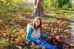 Höstungeflickan med den älsklings- hunden kopplade av i nedgångskog Arkivfoton