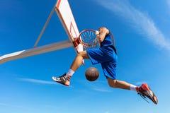 Húmido do Slam Opinião lateral o jogador de basquetebol novo que faz o afundanço foto de stock