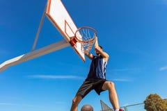 Húmido do Slam Opinião lateral o jogador de basquetebol novo que faz o afundanço fotografia de stock