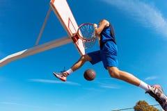 Húmido do Slam Opinião lateral o jogador de basquetebol novo que faz o afundanço imagens de stock