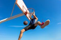 Húmido do Slam Opinião lateral o jogador de basquetebol novo que faz o afundanço imagem de stock royalty free