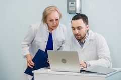 Hübsche ältere Ärztin und hübscher junger Doktor in den weißen medizinischen Mänteln verwenden einen Laptop, die Unterhaltung und stockbilder