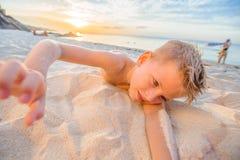 Hübsche acht Jahre Junge auf Strand führt die akrobatischen Skizzen durch Stockfoto