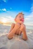 Hübsche acht Jahre Junge auf Strand führt die akrobatischen Skizzen durch Lizenzfreies Stockbild