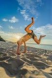 Hübsche acht Jahre Junge auf Strand führt die akrobatischen Skizzen durch Stockbilder