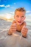 Hübsche acht Jahre Junge auf Strand führt die akrobatischen Skizzen durch Lizenzfreies Stockfoto