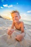 Hübsche acht Jahre Junge auf Strand führt die akrobatischen Skizzen durch Stockbild