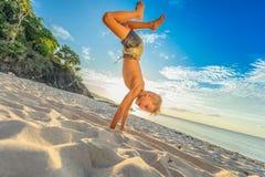 Hübsche acht Jahre Junge auf Strand führt die akrobatischen Skizzen durch Stockfotografie